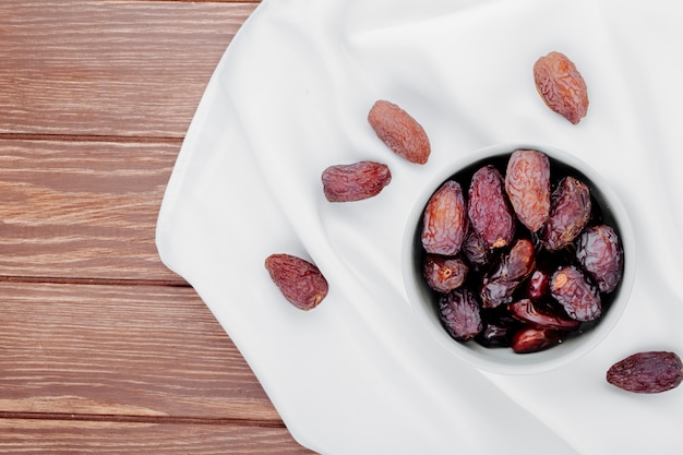 Top view of sweet dried date fruits in a bowl on white tablecloth on wooden background with copy space