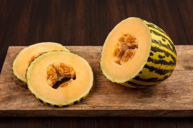 Top view of sweet fresh slices of cantaloupe melon on a wooden kitchen board on a wooden wall