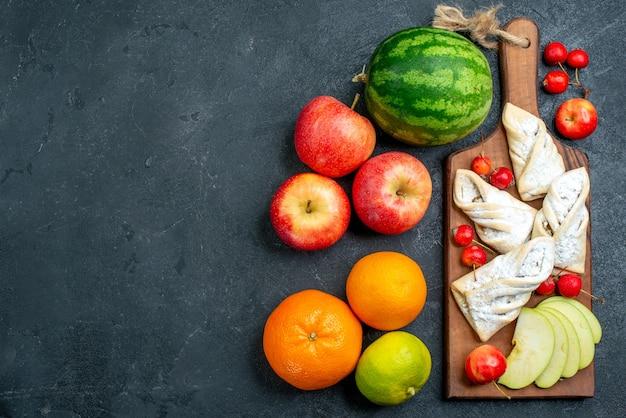 トップビューダークグレーのデスクフルーツビスケットスイートシュガーパイに新鮮なフルーツと甘いフルーティーなペストリー