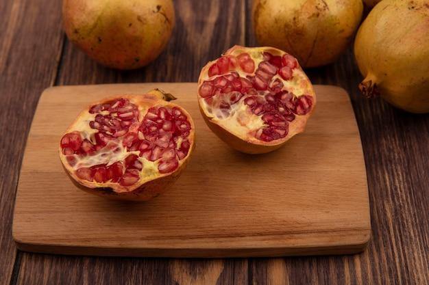 Vista dall'alto di dolce metà melograni su una tavola di cucina in legno con melograni interi isolati su una superficie di legno