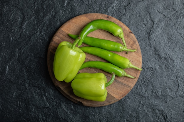 Top view of sweet and hot peppers on wooden board