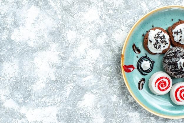 Вид сверху сладкие маленькие пирожные, разные сладкие печенья на светлом белом фоне, пирог, торт, сладкое печенье, печенье, сахар