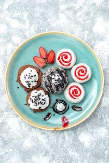 Vista dall'alto dolci piccole torte diversi biscotti dolci su sfondo bianco torta torta biscotto dolce zucchero cookie