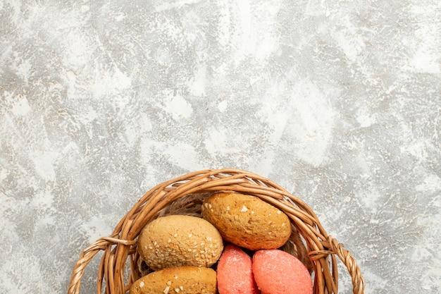Вид сверху сладкие маленькие пирожные внутри корзины на светло-белом фоне