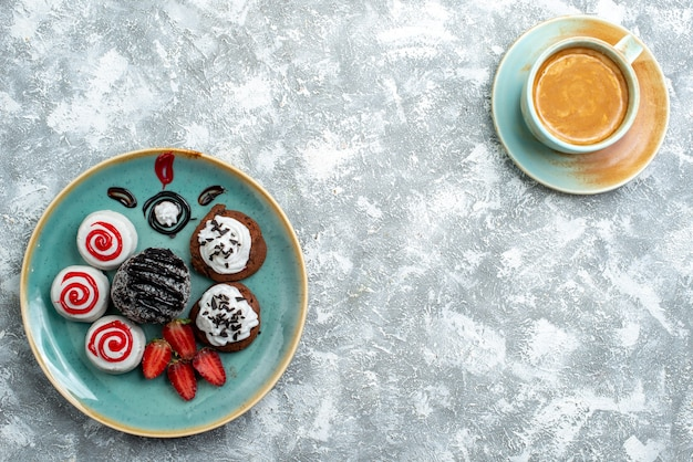 上面図白い背景の上のコーヒーのカップと甘い小さなケーキパイケーキ甘いビスケットシュガークッキー
