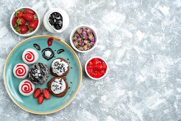 上面図白い背景の上の果物と甘い小さなケーキパイ甘いビスケットクッキーシュガーケーキ