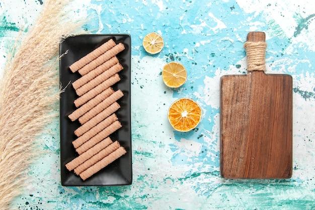 Biscotti lunghi dolci di vista superiore all'interno della tortiera nera sulla torta della torta del tè dello zucchero dolce del biscotto della scrivania blu