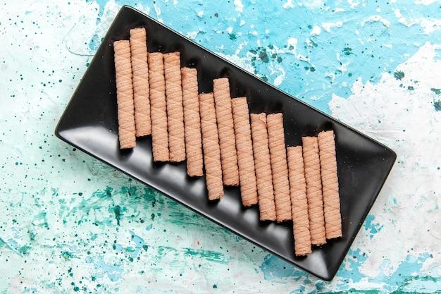Vista dall'alto dolci biscotti lunghi all'interno di una tortiera nera su sfondo azzurro