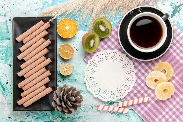 青い机の上にお茶と乾燥パイナップルリングとトップビューの甘い長いクッキー