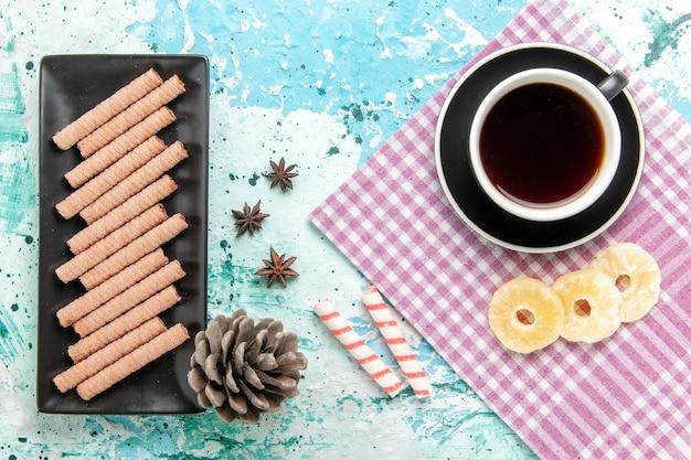 Вид сверху сладкое длинное печенье с чашкой чая и кольцами ананаса на синем фоне