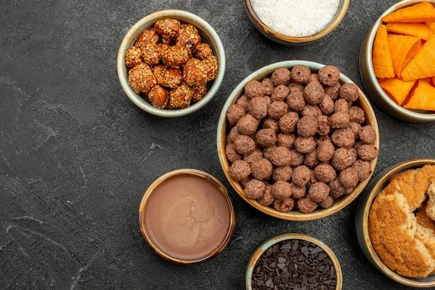 Vista dall'alto di noci dolci con scaglie di cacao e cips sul colore della colazione del pasto al latte spuntino da scrivania scuro