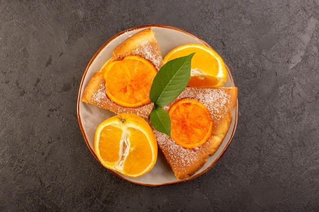 Una vista dall'alto dolce torta all'arancia dolce deliziose fette di torta con fette d'arancia all'interno del piatto rotondo sullo sfondo grigio biscotto zucchero dolce