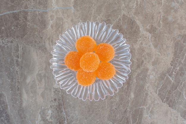 Top view of sweet orange jelly candies on glass plate over grey surface.