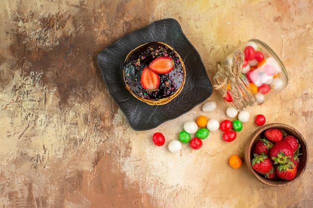 木製の机の上にカラフルなキャンディーとトップビューの甘いパンケーキ