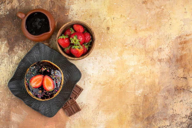 木製の机の上の果物とトップビューの甘いパンケーキ