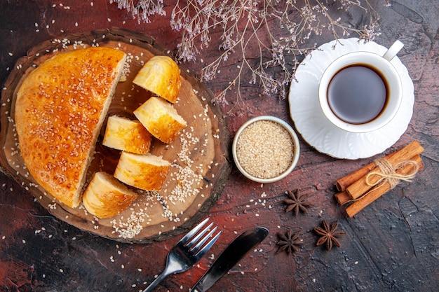 暗い表面でお茶と断片にスライスされた上面図の甘いペストリー