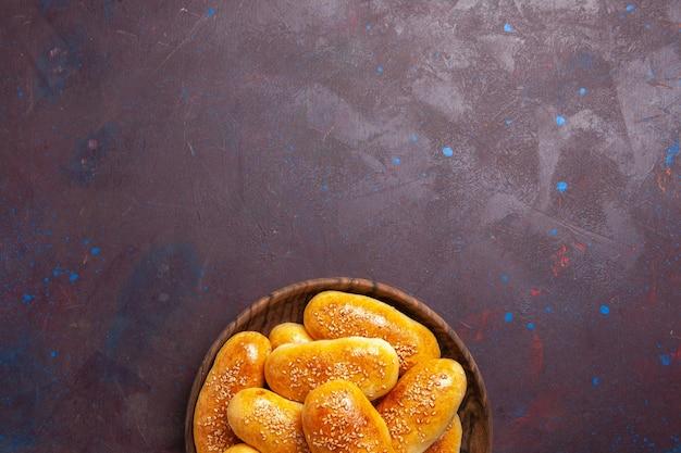 Вид сверху сладкие пирожки вкусное запеченное тесто для чая на темном фоне еда кондитерское тесто чай еда