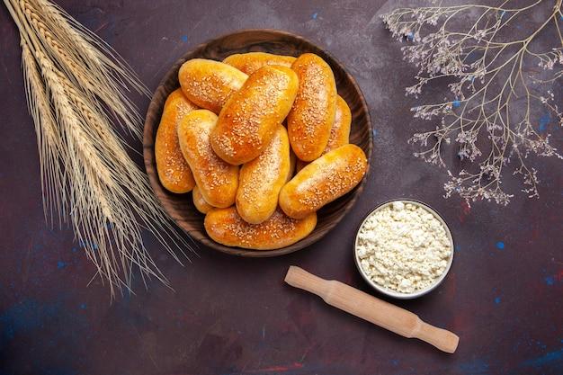 トップビュー甘いパテダークデスクのお茶のためのおいしい焼きパイお茶の食事ペストリー食品パティ生地
