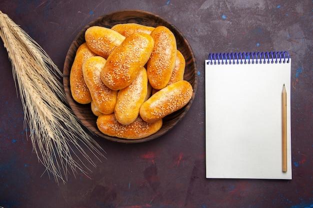 トップビュー甘いパテダークデスクのお茶のためのおいしい焼きパイお茶の食事ペストリーパティ生地食品