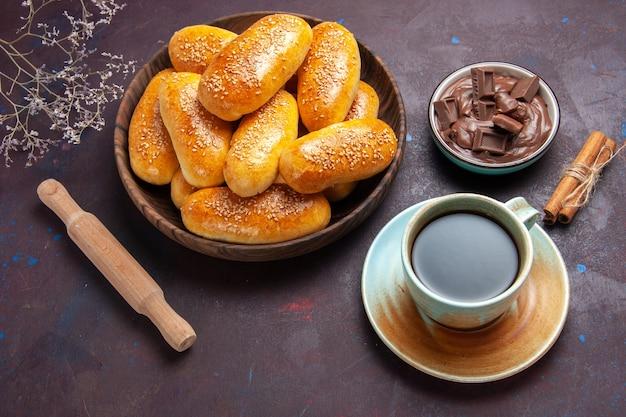 Вид сверху сладкие пирожки с чашкой чая и шоколада на темном фоне, тесто, еда, пирожок, чай