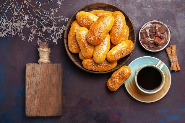 Вид сверху сладкие пирожки с чашкой чая и шоколада на темном фоне, тесто, еда, пирожок
