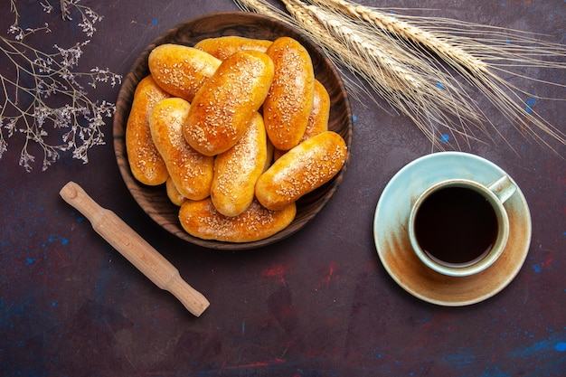 Вид сверху сладкие пирожки с чашкой чая на темном фоне, печенье, еда, пирожок, чай