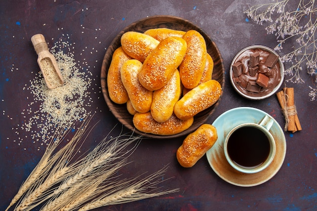 Top view sweet patties with cup of tea and chocolate on dark background meal pastry dough tea food patty