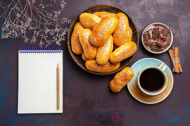 Top view sweet patties with cup of tea and chocolate on dark desk pastry dough meal food patty tea