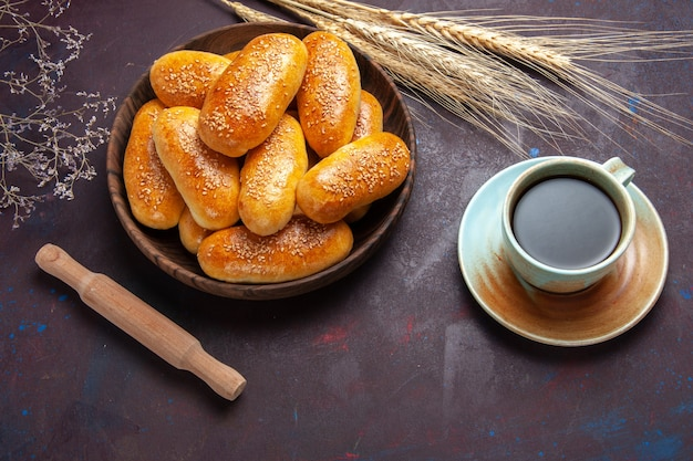 Top view sweet patties with cup of tea on a dark background pastry dough meal food patty tea