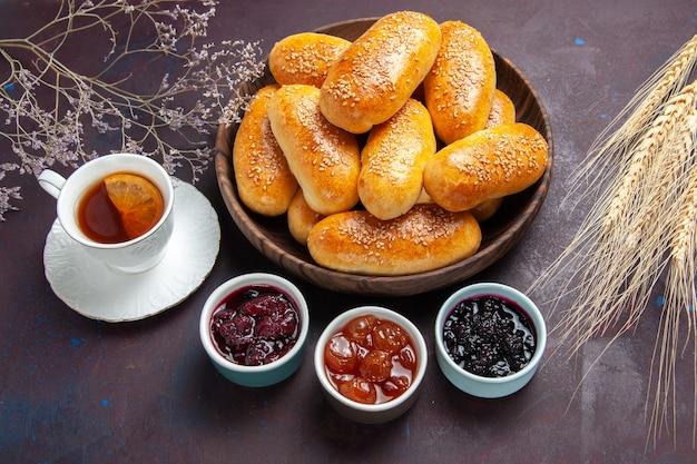 Вид сверху сладкие пирожки с чаем и джемом на темном фоне чайная еда, печенье, пирожки, тесто, еда