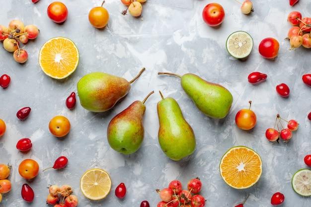 Vista dall'alto di pere dolci con ciliegie e limoni sulla vitamina di bacca di frutta bianca chiara