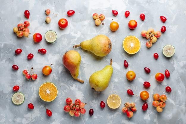 Vista dall'alto di pere dolci con limone e ciliegie sulla scrivania bianca