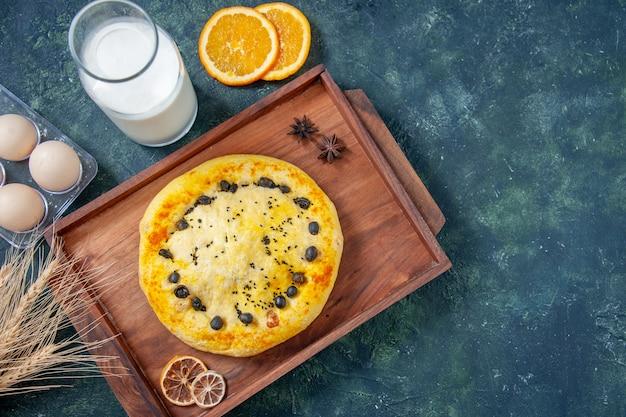 ダークブルーの背景にミルクと甘いパイの上面図ホットケーキ焼きデザートフルーツペストリーケーキパイクッキー