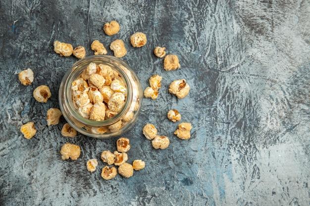 Vista dall'alto popcorn dolce all'interno della latta di vetro sulla superficie chiara