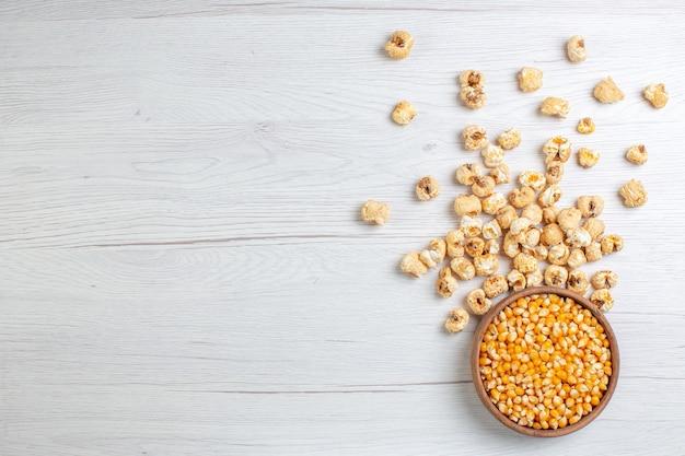Popcorn dolce vista dall'alto con semi crudi su superficie chiara