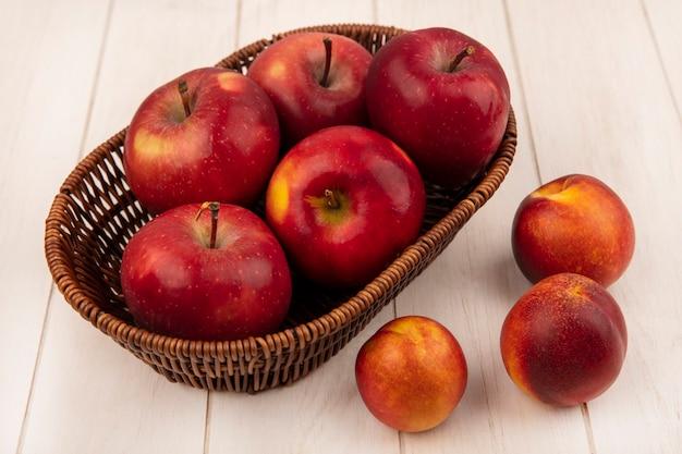Vista dall'alto di mele rosse dolci su un secchio con pesche isolato su una parete di legno bianca