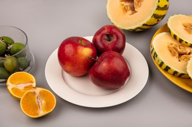 Top view of sweet red apples on a white plate with slices of cantaloupe melon on a yellow plate with tangerines isolated on a grey wall