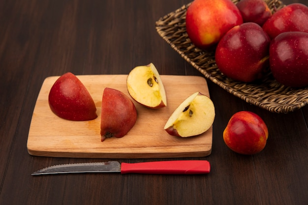 Top view of sweet red apples on a wicker tray with apple slices on a wooden kitchen board with knife on a wooden wall