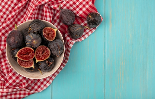 Top view of sweet ripe black mission figs on a bowl on a checked cloth on a blue wooden wall with copy space