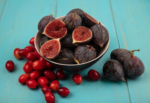 Top view of sweet ripe black mission figs on a bowl with cornelian cherries isolated on a blue wooden wall