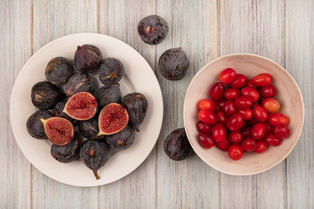 Top view of sweet ripe black mission figs on a white bowl with cornelian cherries on a bowl on a grey wooden background