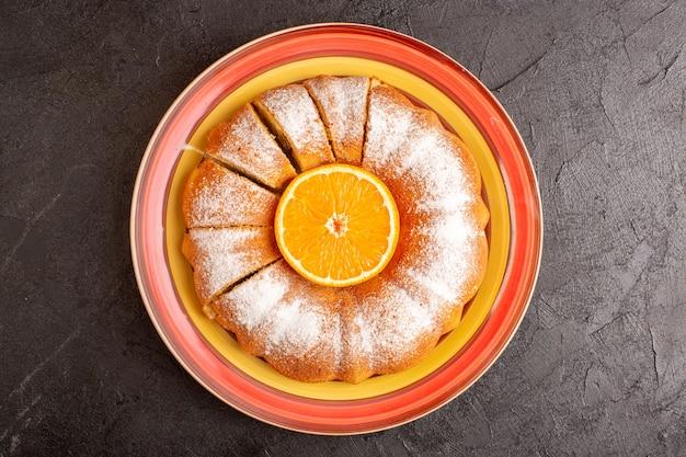 Una torta rotonda dolce di vista superiore con zucchero in polvere e arancia nel mezzo affettato dolce delizioso piatto interno sullo sfondo grigio biscotto di zucchero biscotto