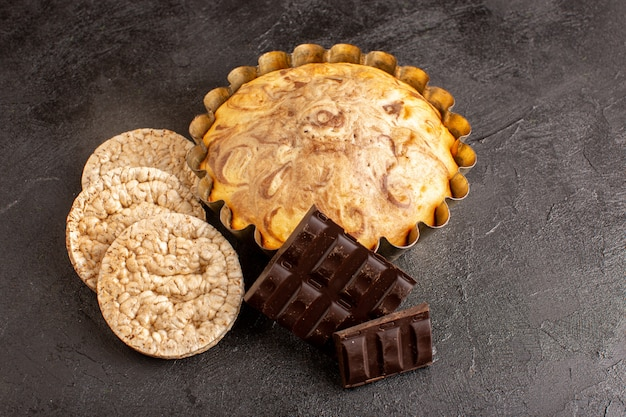 A top view sweet round cake yummy delicious inside cake pan along with choco bars and bread crisps on the grey background biscuit sugar cookie