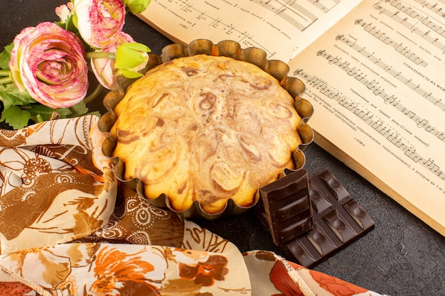 A top view sweet round cake yummy delicious inside cake pan along with choco bars flowers and music notes copybook on the grey background biscuit sugar cookie