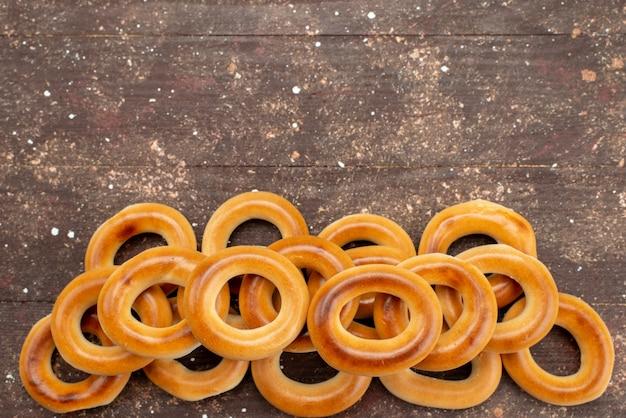 Вид сверху сладкие круглые сухарики и вкусные закуски на коричневом, печенье бисквитный напиток