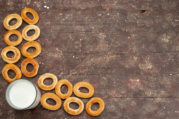 Вид сверху сладкие круглые крекеры сушат вместе со стаканом холодного молока на коричневом, печенье печенье бисквит завтрак