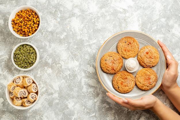 Biscotti dolci della sabbia di vista superiore con i semi su fondo bianco
