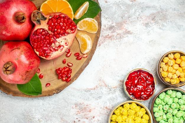 Вид сверху сладкие леденцы со свежими фруктами на белом фоне сахарные конфеты фруктовые сладости