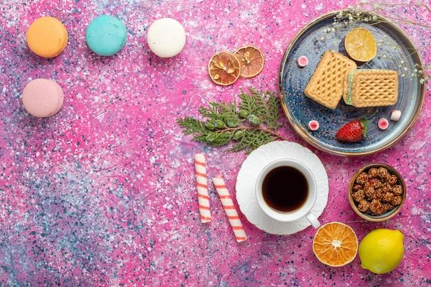 Vista dall'alto di cialde dolci con tazza di tè e macarons sulla superficie rosa