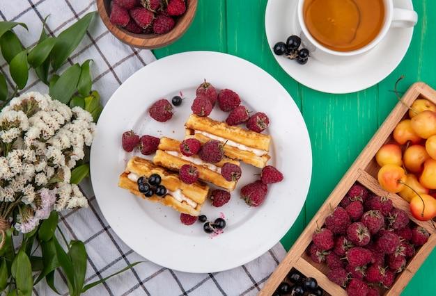 Вид сверху сладкие вафли с малиной на тарелке с белой вишней и цветами на клетчатом полотенце